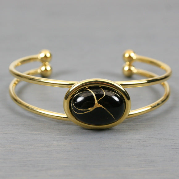 Black onyx kintsugi bracelet with a gold cuff setting