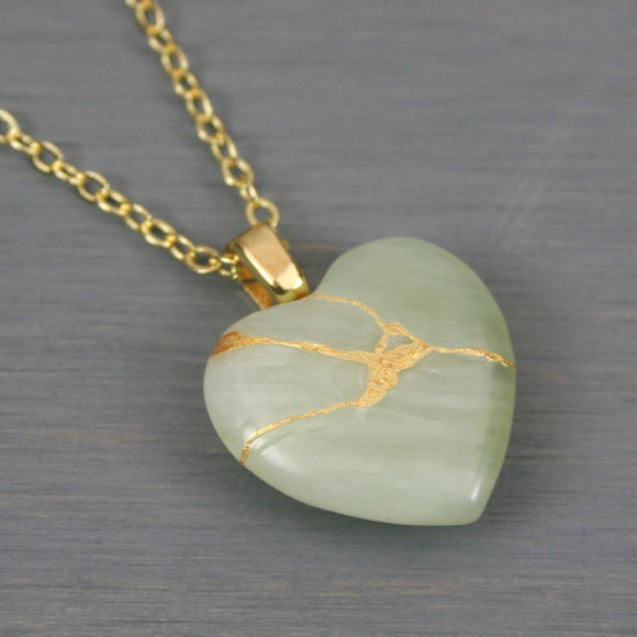 Light green stone broken heart pendant with kintsugi repair on a chain necklace