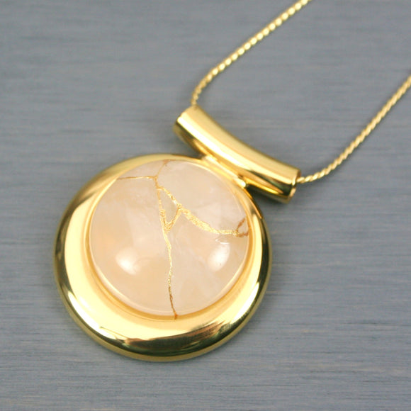 Rose quartz kintsugi pendant in a gold setting on chain