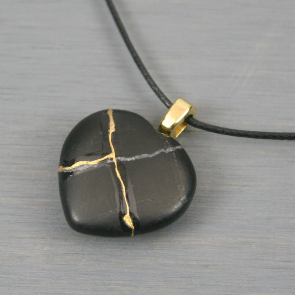 Black stone broken heart pendant with kintsugi repair on black cotton cord