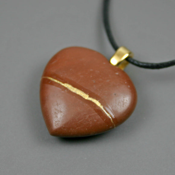 Reddish brown stone broken heart pendant with kintsugi repair on black cotton cord from A Kintsugi Life