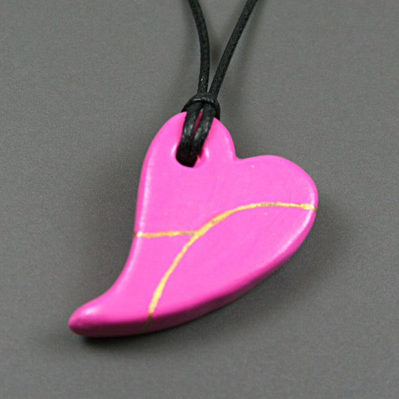 Pink faux kintsugi broken heart pendant on black cotton cord from A Kintsugi Life