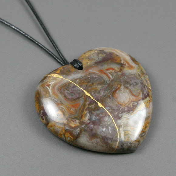 Brown agate broken heart pendant with kintsugi repair on black cotton cord from A Kintsugi Life