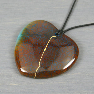 Brown and blue dragon veins agate broken heart pendant with kintsugi repair on black cotton cord from A Kintsugi Life