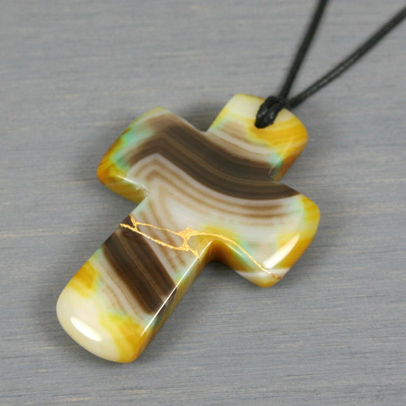 Yellow and brown banded agate kintsugi cross pendant on black cotton cord necklace from A Kintsugi Life