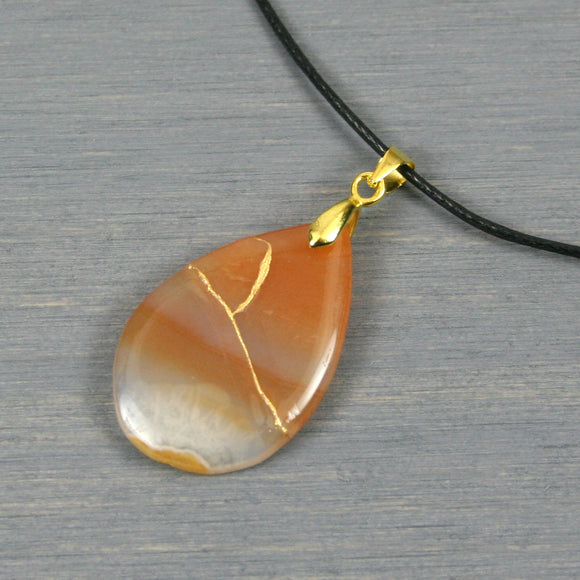 Red banded agate teardrop pendant with kintsugi repair on black cotton cord from A Kintsugi Life