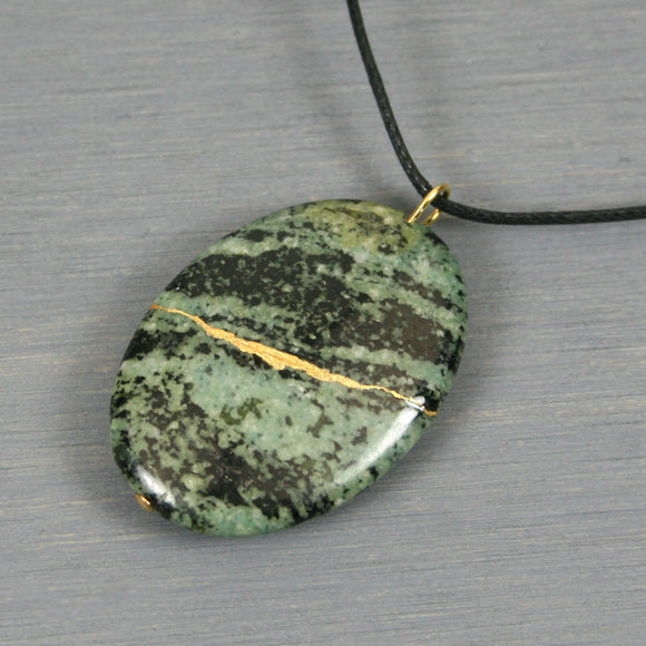 Green zebra jasper pendant with kintsugi repair on black cotton cord from A Kintsugi Life