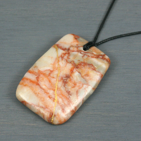 Redline marble pendant with kintsugi repair on black cotton cord from A Kintsugi Life
