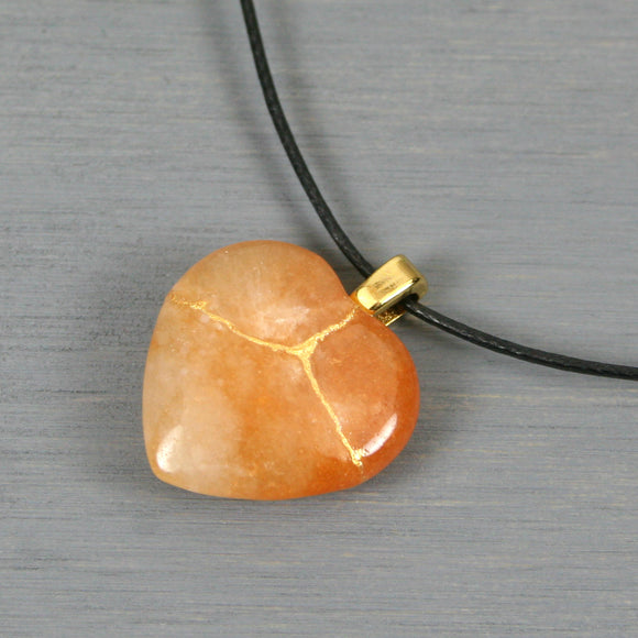Red aventurine broken heart pendant with kintsugi repair on black cotton cord from A Kintsugi Life