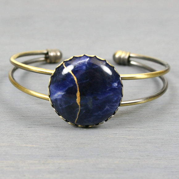Sodalite kintsugi bracelet in an antiqued brass cuff bangle setting from A Kintsugi Life