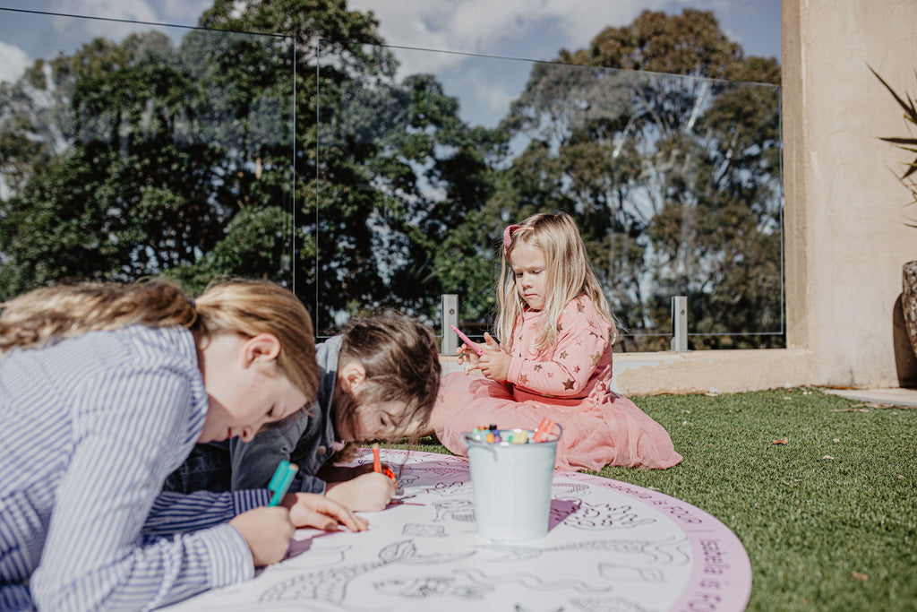 Mermaid colouring in - three girls colouring in on the grass
