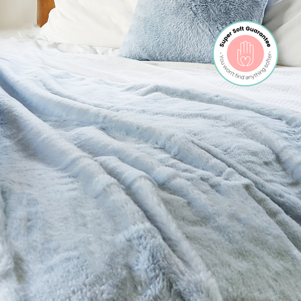 Fluffy blanket on bed in bedroom. Faux Fur in blue. Comfy, cosy home decor products.