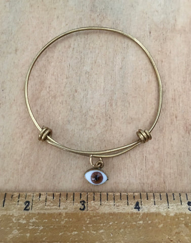 Adjustable brass bangle with brown eye dangle