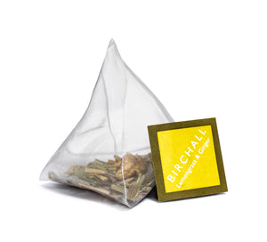 A single prism yellow tagged tea bag of Birchall Lemongrass & ginger tea. Mesh tea bag with large loose leaf inside.