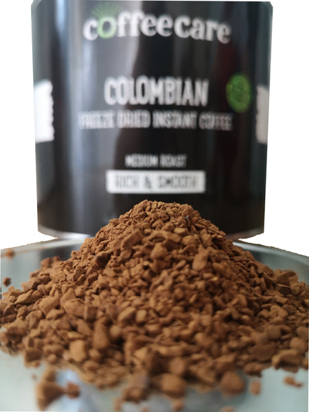 a pile of Coffee Care's Colombian Freeze Dried Instant Coffee. 500g of arabica coffee. Medium roast, rich and smooth. Tin blurred out in background
