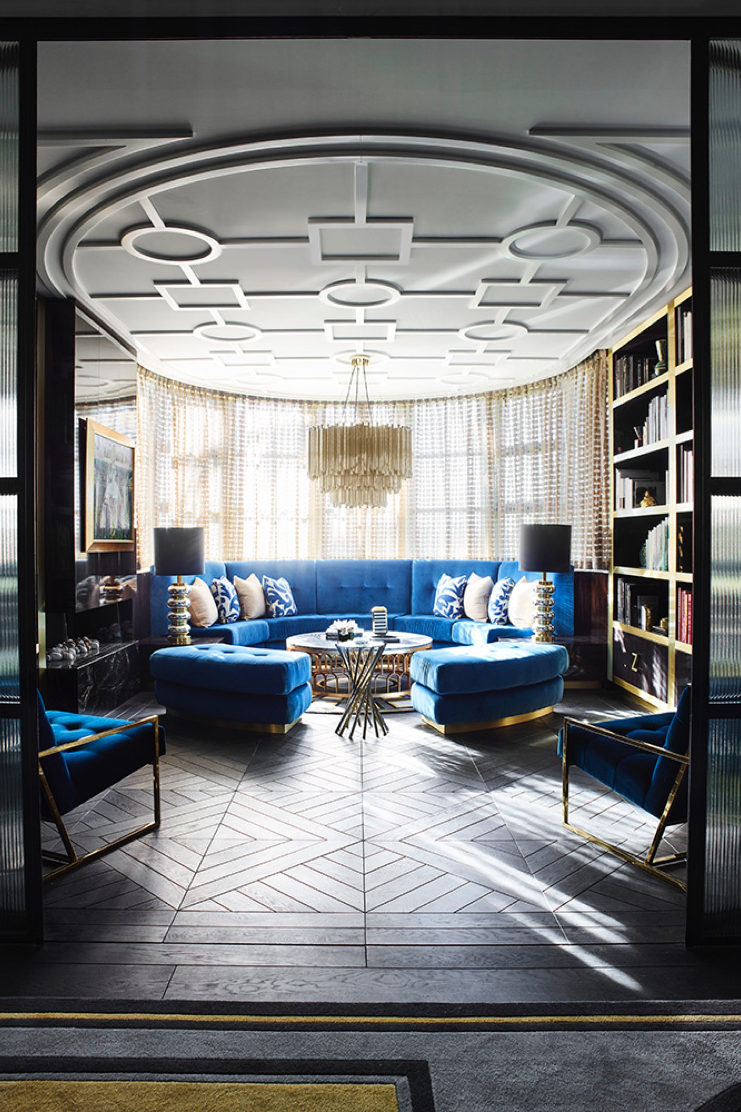 Living room with blue curved sofa and geometric ceiling design