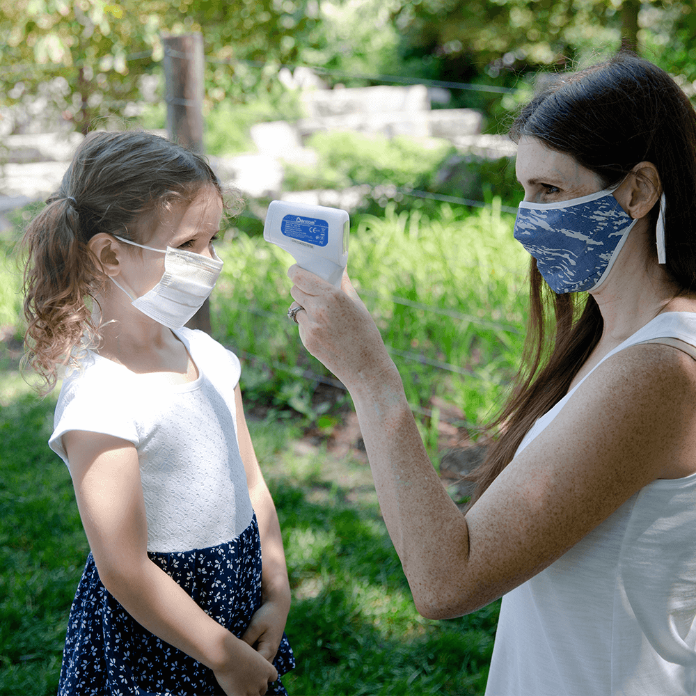 mom in face mask takes the temperature using a non-contact infrared thermometer of daughter also wearing face mask