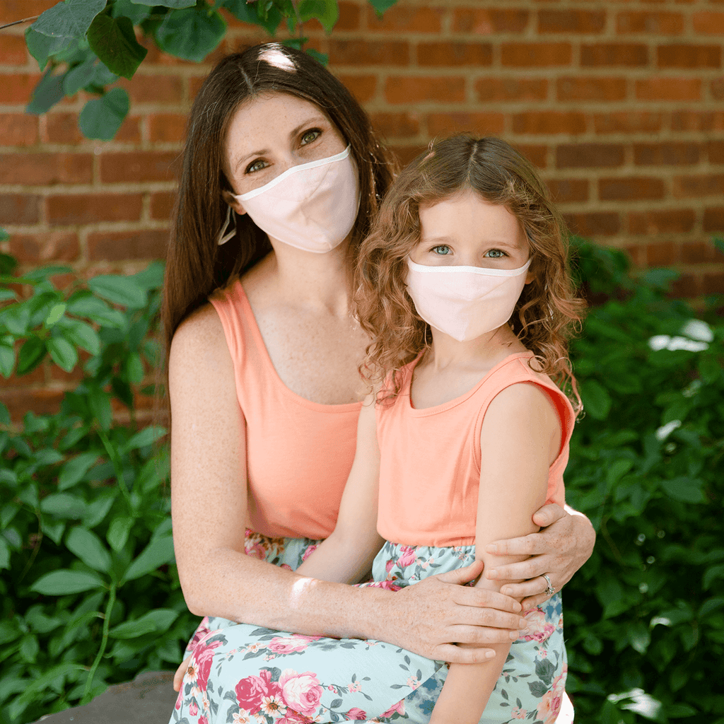 mom and daughter with matching solid pink face masks