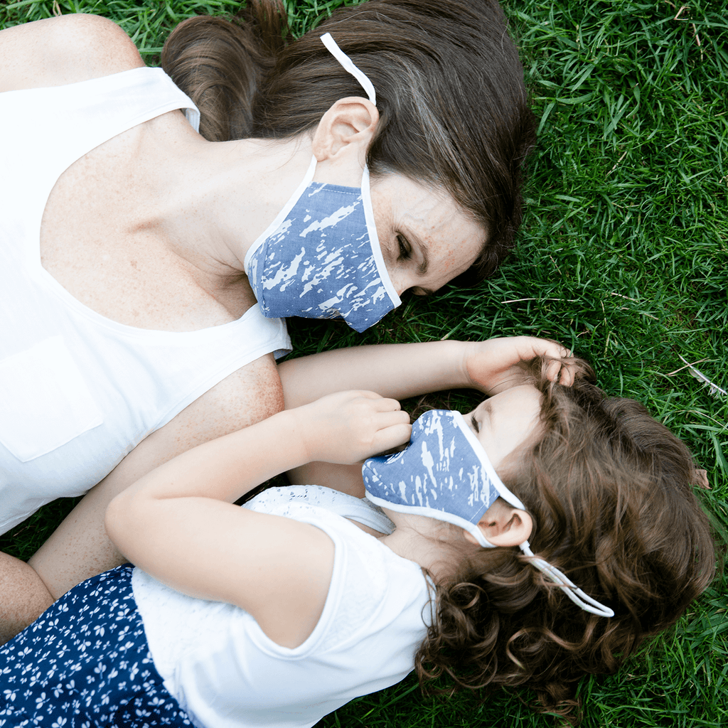 mom annd daughter happlily lie in grass with matching grey printed face masks