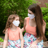 mom and daughter sit outside with matching face masks