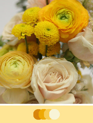 Close up image of DIY Bridal Bouquet with yellow tones. Flowers include billy balls, astilbe, ranunculus, button poms, roses, waxflower baby's breath and carnations