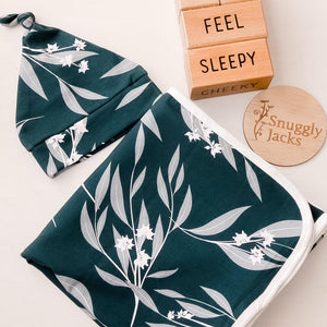 100cm x 100cm Soft and breathable stretch swaddle wrap with matching beanie. Made from 95% cotton and 5% Spandex our organic swaddle wraps have the perfect amount of stretch to keep your babies snug during sleep time. Eucalyptus print on a deep blue-green background