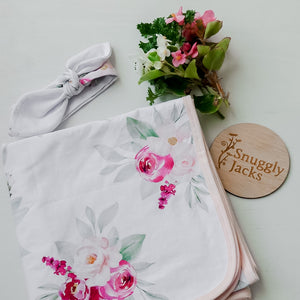 100cm x 100cm Soft and breathable stretch swaddle wrap with matching top knot. Made from 95% cotton and 5% Spandex our organic swaddle wraps have the perfect amount of stretch to keep your babies snug during sleep time. Floral print with pink and pastel pink flowers on a white background