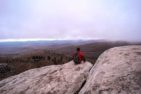 hiker sitting on cliff overlooking the blue ridge parkway from rough ridge