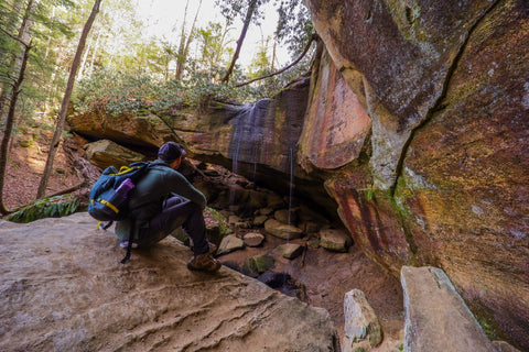hiker sitting atop boulder overlooking whittleton arch in red river gorge kenucky