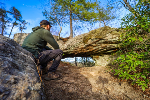 Hiker sitting in front of arch of triumph red River Gorge kentucky
