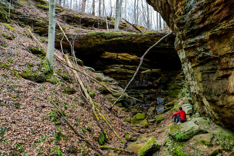 Hiker sitting in front of ravine arch in yellow birch ravine nature preserve Indiana