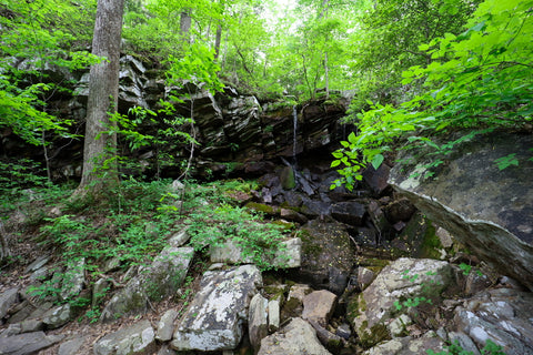 Waterfall streaming over rock shelter in Denny Cove within south Cumberland State Park in Tennessee