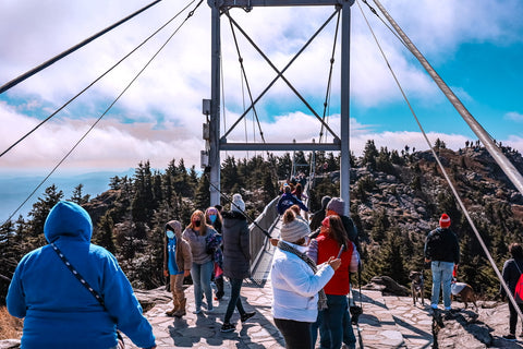 hikers waiting to cross over mile high swinging bridge on grandfather mountain