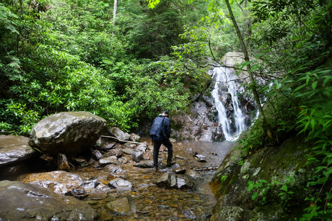 hiker viewing waterfall cascading down boulders along cabin creek trail in grayson highlands state park