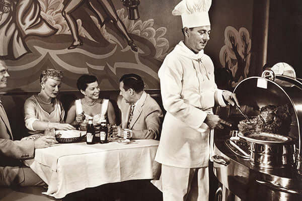 Historic black and white photo of a man in chef's whites carving prime rib from a silver cart