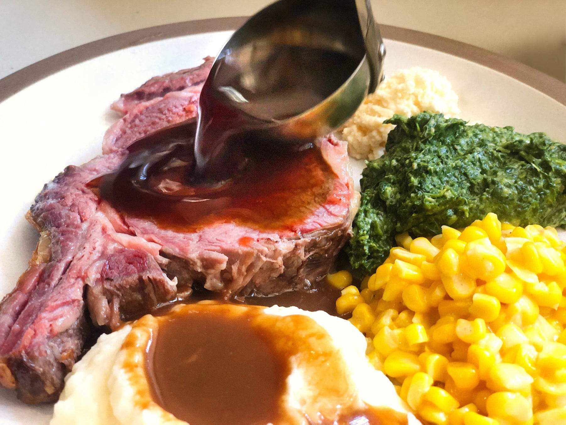 pouring au jus on a cut of prime rib