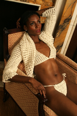 Sexy pretty woman with long black hair wearing CharmaineLouiseIntimates CLIntimates Lena cream cashmere sweaterlette sweater crochet bra crochet string bikini reclining on chair