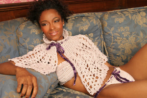 Sexy pretty woman wearing CharmaineLouiseIntimates CLIntimates Ginger purple cashmere silk crochet cape capelet bandeau bra purple velvet crochet string bikini reclining on sofa