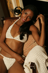 Sexy pretty woman with long black hair wearing CharmaineLouise Intimates CLIntimates Lena cream cashmere sweaterlette sweater cardigan crochet bra crochet string bikini reclining on chair