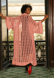 Sexy pretty woman wearing CharmaineLouise Intimates CLIntimates Diana pink cashmere crochet kimono robe black sheath dress heels standing in window
