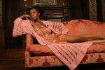Sexy pretty woman wearing CharmaineLouise Intimates CLIntimates Diana pink cashmere crochet kimono robe pink gold minidress reclining on sofa