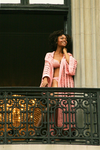 Sexy pretty woman wearing CharmaineLouise Intimates CLIntimates Diana pink cashmere crochet kimono robe crochet bra string bikini standing on balcony