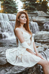 CharmaineLouise Books CLBooks Sexy pretty Dominatrix sub switch woman with long red hair wearing white lace bustier under unbuttoned short white dress sitting by waterfall