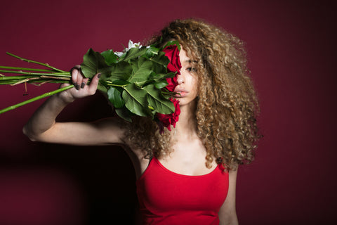 CharmaineLouise Books CLBooks Sexy pretty Dominatrix woman with long curly brown blonde hair wearing red fitted tank top holding red roses