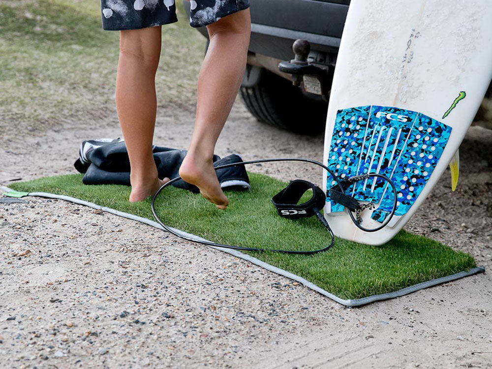 Young surfer uses the muk mat to clean his feet and protect his surfboard and wetsuit from the rocky road before he hops in the car.