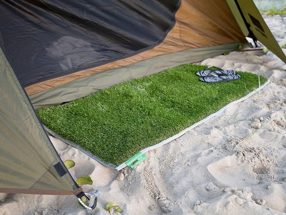 Image of the muk mat placed on the sand outside of a tent holding a pair of thongs.