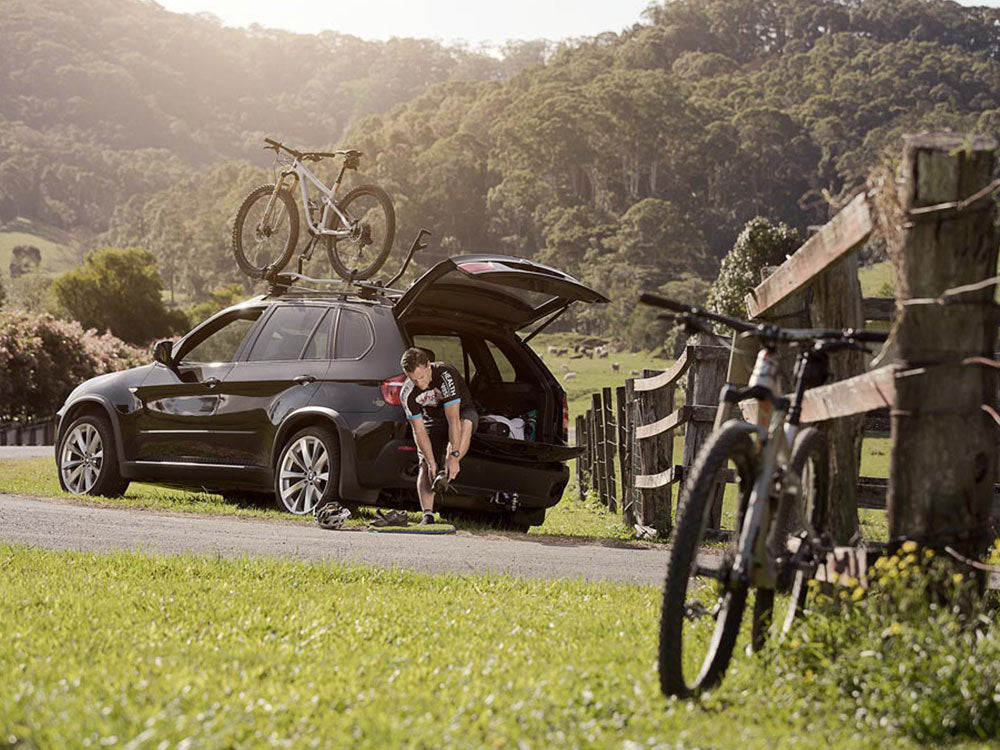 Image of mountain biker using his muk mat to take off his dirty cleats before hopping in the car and heading home.