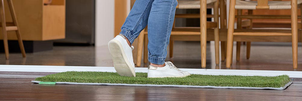 Image of woman using her muk mat to wipe her feet before entering the home.