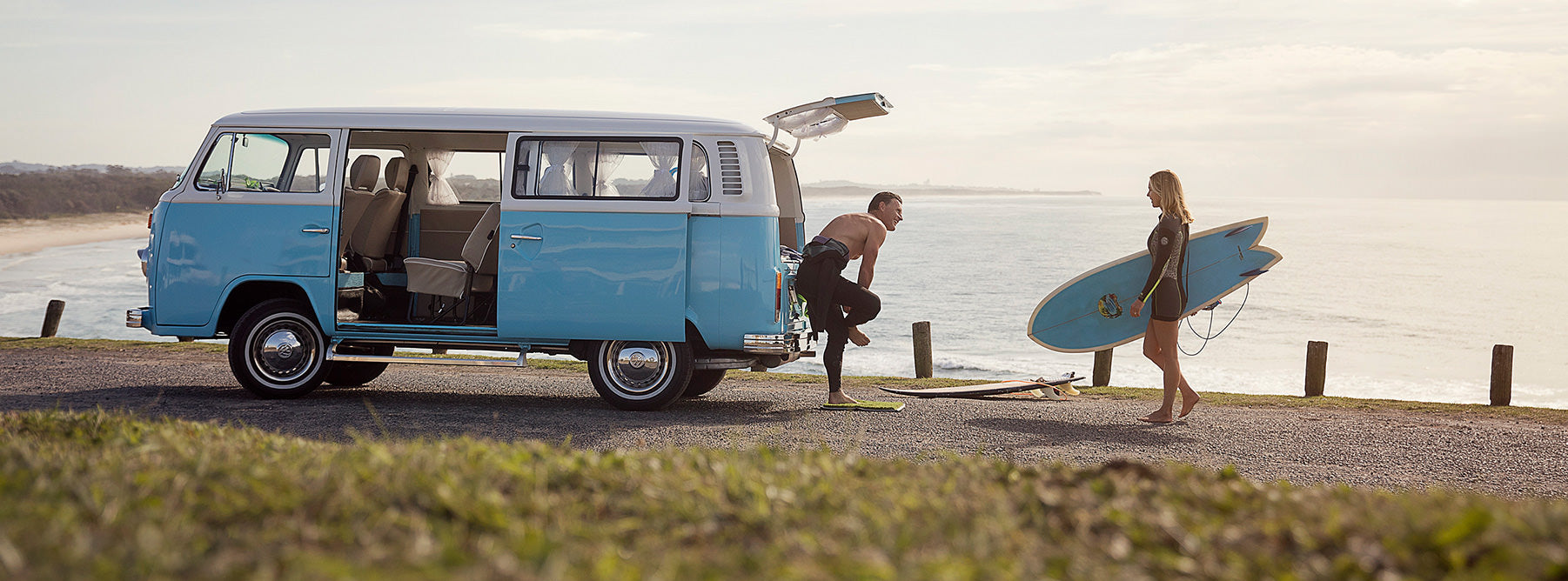 Young couple coming in from a surf wearing wetsuits and carrying surfboards, using their new grass mat online purchase to clean their feet before hopping in their blue Kombi Van.