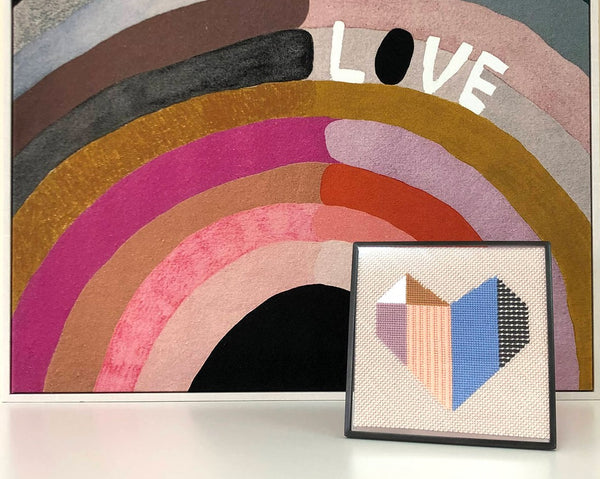 framed needlepoint with illustration of geometric heart next to paiting with rainbow